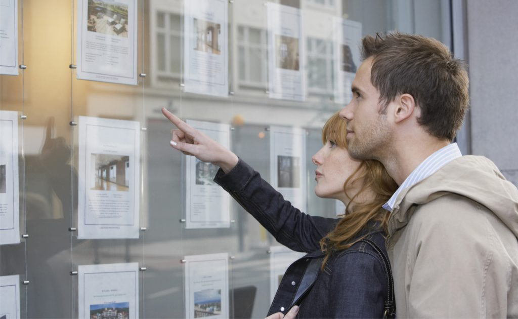 man and woman looking at images of properties