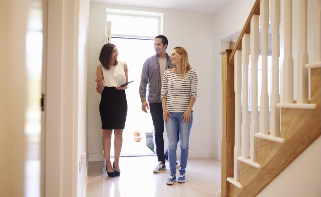 estate agent walks through the front door of a home with a couple