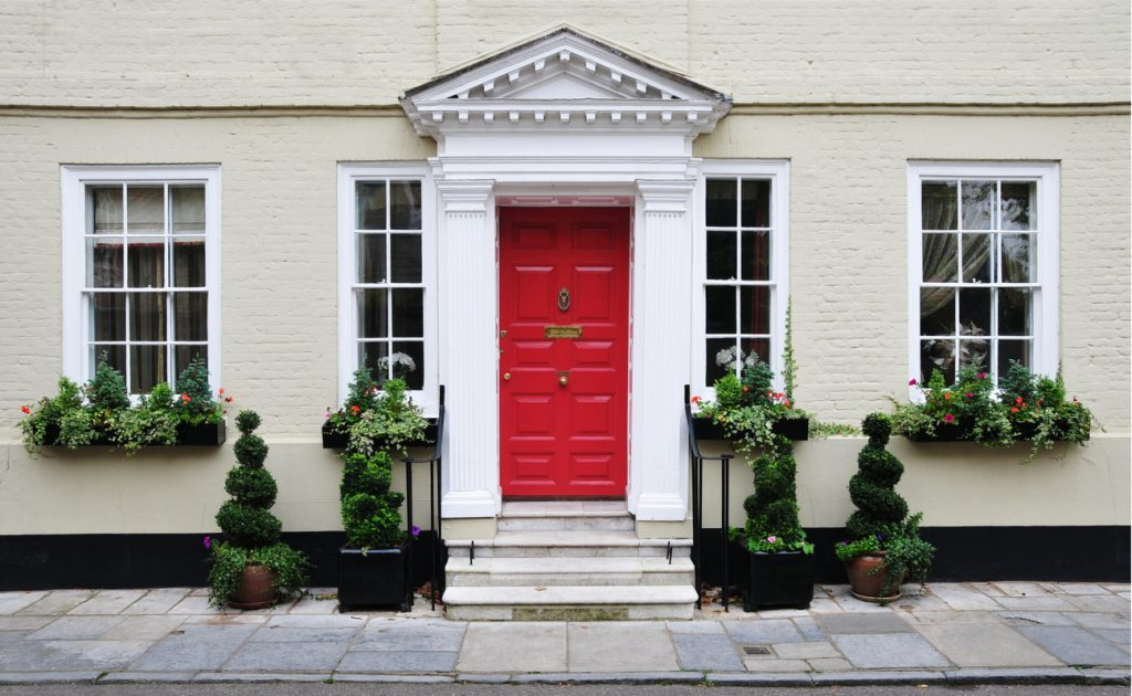 exterior of Georgian home with red front door and plants on kerb