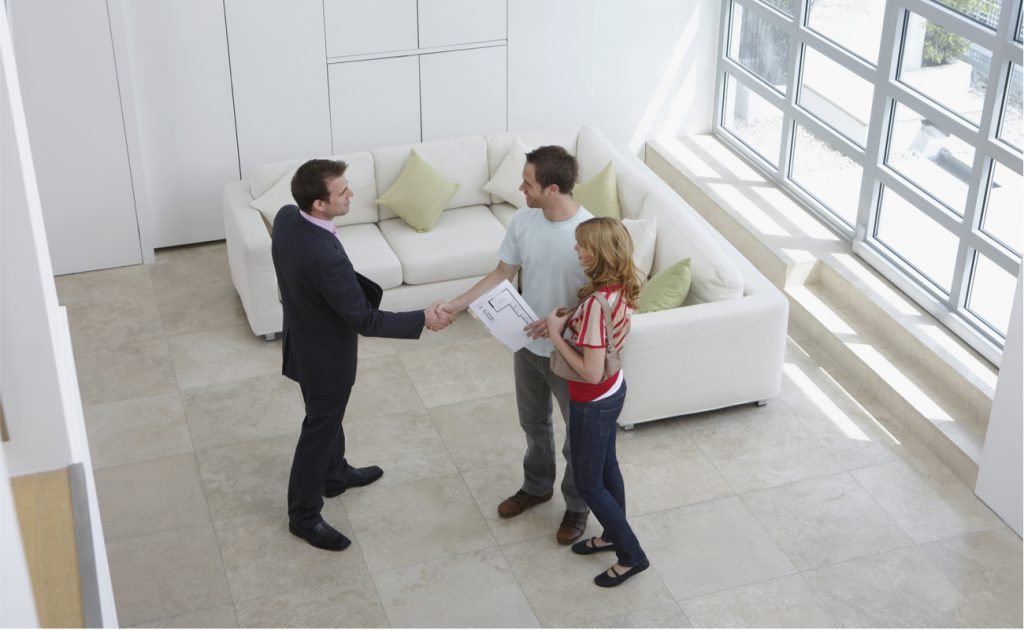 estate agent shakes hand with couple while viewing apartment