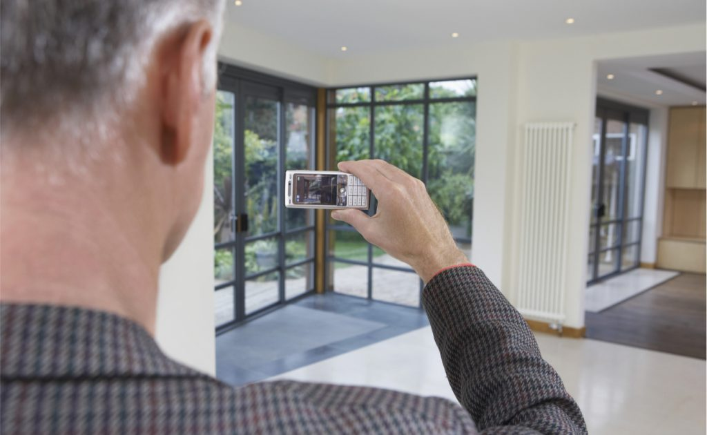 man taking a photograph of windows using mobile phone