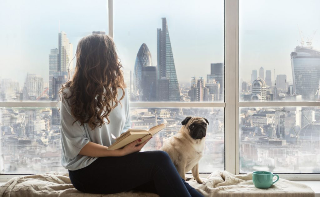 woman with dog looking out high rise apartment window at London skyline