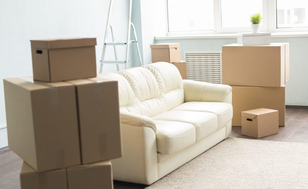pile of moving boxes on either side of a white couch