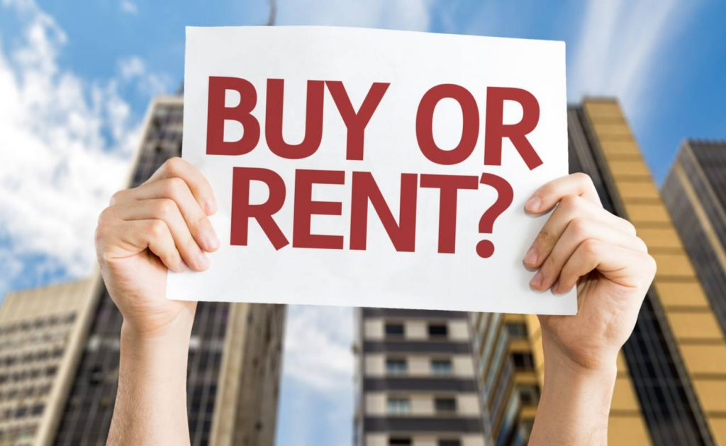 hands holding up sign saying buy or rent with apartments in background