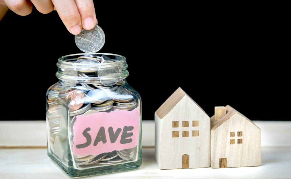 saving coins to buy a house in glass jar with save written on it