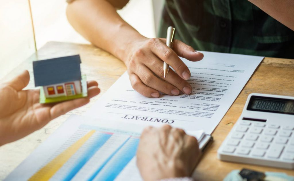 estate agent hand holding a house and buyer signing contract with calculator