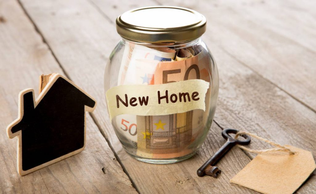 concept of saving money for a new home with euros in glass jar