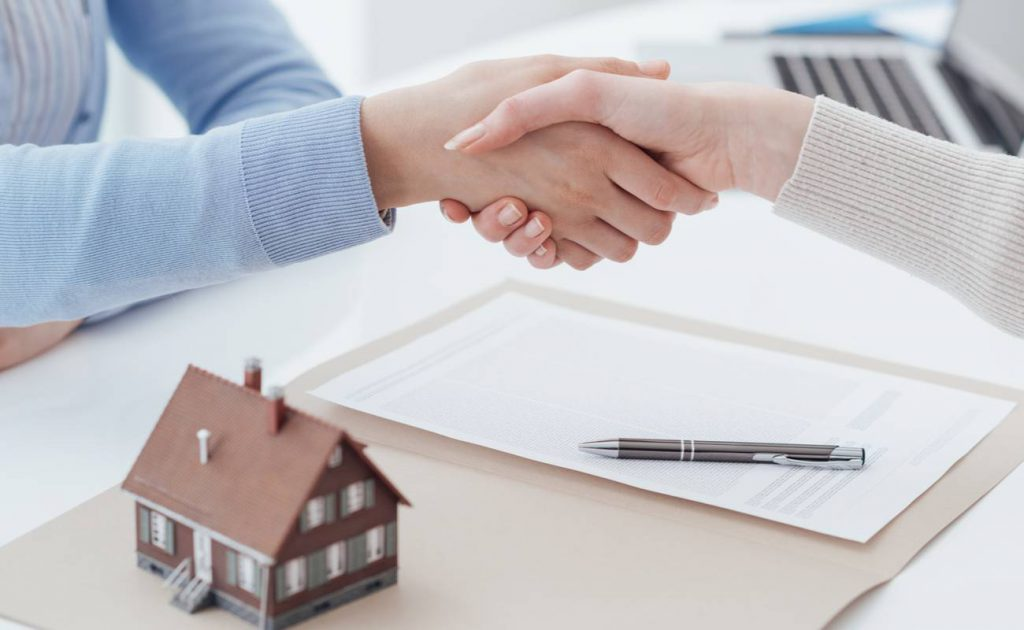 Two women shaking hands over house and signed paperwork