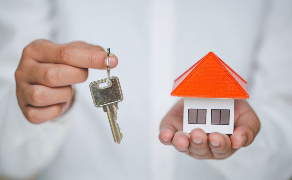 Hands holding keys and small model house