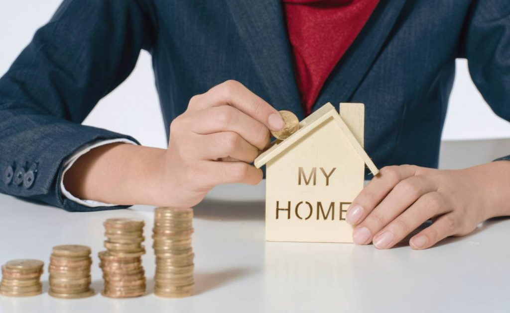 Man with money saving in small wooden model house